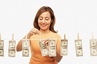 Hispanic woman hanging dollar bills on clothes line