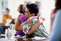 Grandmother and Grandson Hugging in Restaurant