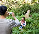Asian man taking photograph of girlfriend in woods