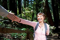 Asian woman reaching for hand in woods