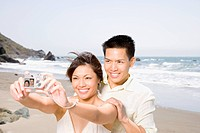 Asian couple taking own photograph at beach