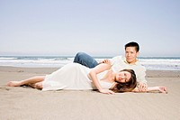 Asian couple laying on beach