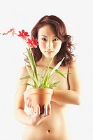 Nude Asian woman holding potted plant