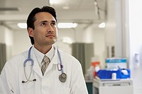 Hispanic male doctor looking up