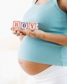 Pregnant African American woman holding &#8220;BOY&#8221; blocks