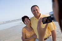 Hispanic couple being video recorded at beach