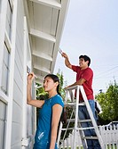 Multi-ethnic couple painting house