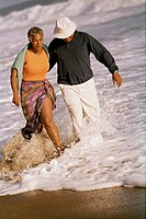 Senior African American couple walking in surf