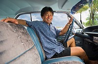 Asian man sitting in car
