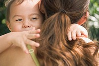 Hispanic baby hugging mother (thumbnail)