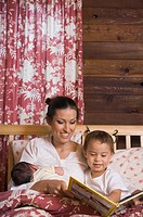 Hispanic mother reading to daughter (thumbnail)