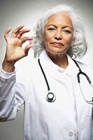 Senior Hispanic female doctor holding medication