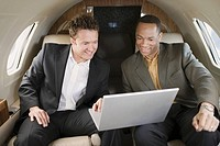Multi-ethnic businessmen on airplane