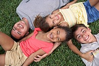 Hispanic father and children laying in grass