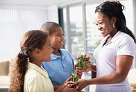 African American mother receiving flowers from children