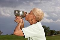 Senior African American woman kissing golf trophy