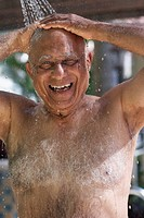 Senior Mixed Race man in outdoor shower