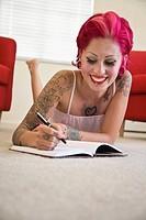 Tattooed Hispanic woman writing in journal