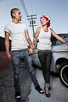 Tattooed Hispanic couple smiling at each other