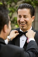 Hispanic man having bowtie adjusted