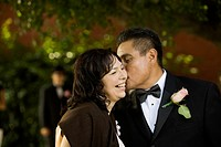 Hispanic man kissing wife on cheek