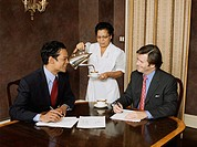 Hispanic maid pouring coffee for businessmen