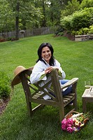 Hispanic woman sitting in backyard