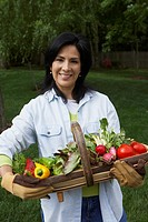 Hispanic woman holding fresh vegetables