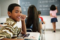 Hispanic boy at desk in classroom