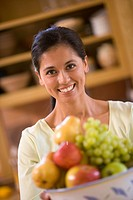 Hispanic woman holding bowl of fruit