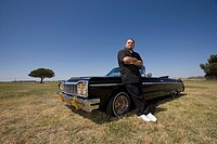 Hispanic man leaning on low rider car