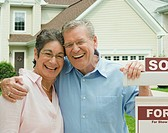 Senior couple in front of new house