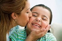 Hispanic mother kissing daughter on cheek