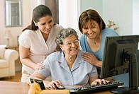 Hispanic grandmother, mother and daughter looking at computer