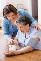 Senior Hispanic woman taking own blood pressure