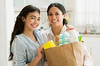 Hispanic mother and daughter with grocery bag