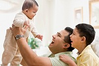 Hispanic father and son smiling at baby