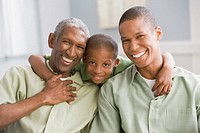 African American grandfather, father and son hugging