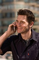 A man smiles as he talks on a cellphone outside