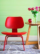 A bright red chair and a side table with flowers on it
