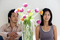 Asian couple looking at flowers in vase
