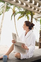 Asian woman in bathrobe reading newspaper