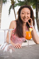 Asian woman with cocktail at beach bar