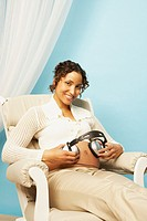 Pregnant Mixed Race woman holding headphones on belly