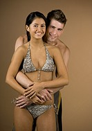 Multi-ethnic couple hugging in bathing suits