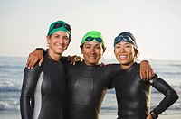 Multi-ethnic women wearing wetsuits and goggles