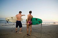 Multi-ethnic couple holding surfboards