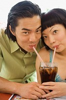 Asian couple drinking soda with straws