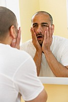 Middle Eastern man looking in mirror