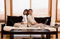 Hispanic couple sitting back to back on sofa